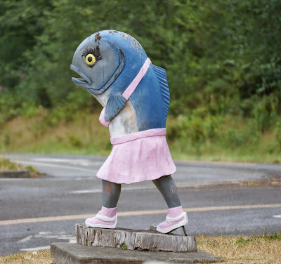 carving of a walking salmon is skirt, halter top, and sneakers