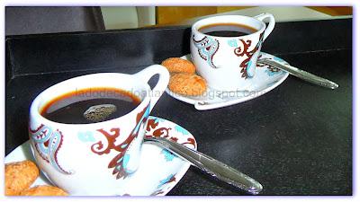 Foto de duas xícaras com café servido com bolachas de amêndoas.