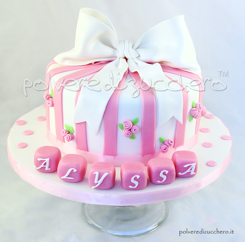 torta battesimo per una bimba in bianco e rosa, con fiocco e roselline in pasta di zucchero