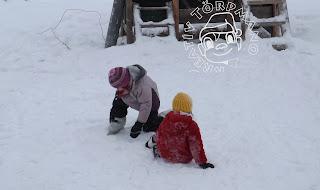 SZöveg: Ha már jól megy neki amúgy is a korcsolyázás, akkor nem okoz számára problémát az egyenlőtlen terep, ha még csak most tanul, akkor meg úgyis mindegy: esni fog akár sima a pálya, akár nem. Kép:  A két gyerek a még eléggé havas korcsolyapályáról próbál feltápászkodni.