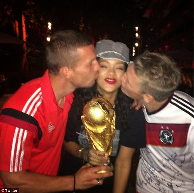 Rihanna shared a picture of her clutching the cup while being kissed by players Podolski and Schweinsteiger
