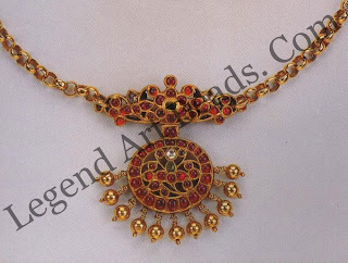 NECKLACE South India; early 20'h century Private collection A ruby and diamond fan shaped pendant fringed with gold beads is strung on a gold-link chain referred to as The pocket-watch chain (geddiyara sangili)