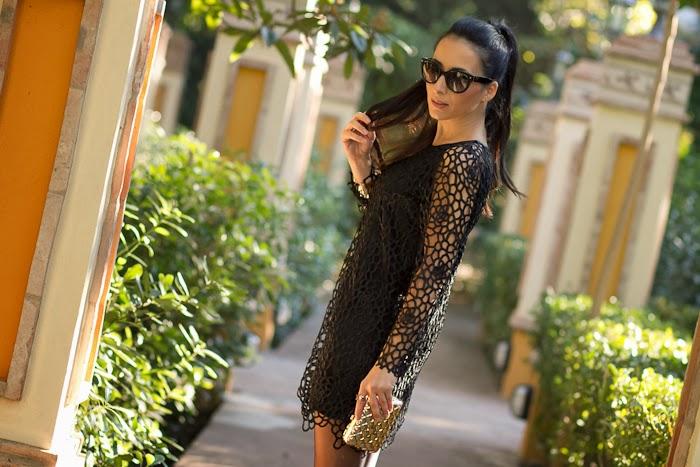 Vestido negro recortado y clutch metálico dorado con Gafas 17Os de Prada