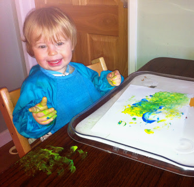 Child now looking pleased with himself - paint on table too!