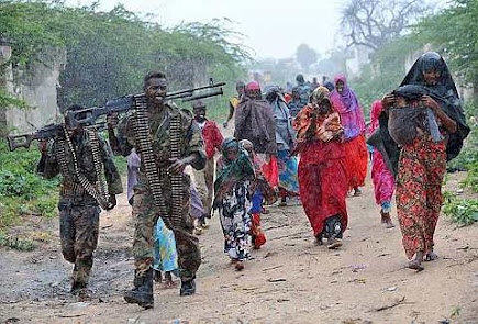 Somali woman and children are escorted in the rain by soldiers