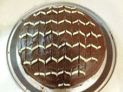 bird's eye view of chocolate cake decorated with alternating curly white stripes
