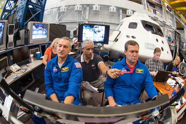 Astronauts Rick Linnehan and Mike Foreman work with simulation instructor Juan Garriga (center) to prepare for their first ascent simulation inside a mockup of NASA's new Orion spacecraft at Johnson Space Center. Image Credit: NASA