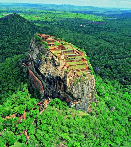 Sigiriya (Lion's rock) is a place with a large stone and ancient rock fortress and palace ruin in the central Matale District of Central Province, Sri Lanka, surrounded by the remains of an extensive network of gardens, reservoirs, and other structures. Sigiriya is also renowned for its ancient paintings (frescos), which are reminiscent of the Ajanta Caves of India. It is one of the eight World Heritage Sites of Sri Lanka.  Sigiriya may have been inhabited through prehistoric times. It was used as a rock-shelter mountain monastery from about the 5th century BC, with caves prepared and donated by devotees of the Buddhist Sangha. According to the chronicles as Mahavamsa the entire complex was built by King Kashyapa (477 – AD 495), and after the king's death, it was used as a Buddhist monastery until 14th century.  Sigiriya is considered one of the most important urban planning sites of the first millennium, and the site plan is considered very elaborate and imaginative. The plan combined concepts of symmetry and asymmetry to intentionally interlock the man-made geometrical and natural forms of the surroundings. On the west side of the rock lies a park for the royals, laid out on a symmetrical plan; the park contains water-retaining structures, including sophisticated surface/subsurface hydraulic systems, some of which are working even today. The south contains a man-made reservoir; these were extensively used from the previous capital of the dry zone of Sri Lanka. Five gates were placed at entrances.