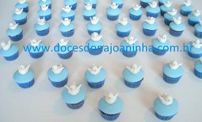 Mini cupcakes em azul decorados com pombinha branca para batizado