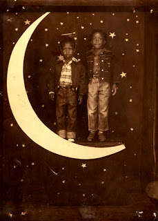 Two boys standing on a crescent moon with a starry backdrop