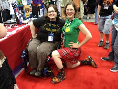 Author cosplaying Oracle, using blue wheelchair, wearing black Batman logo shirt with brown cargo pants & headset, posed with Jennie Breeden wearing red plaid kilt, green shirt, & funky boots