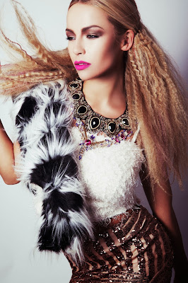 Model wears faux fur with big textured hair and strong makeup for a glam vibe photoshoot