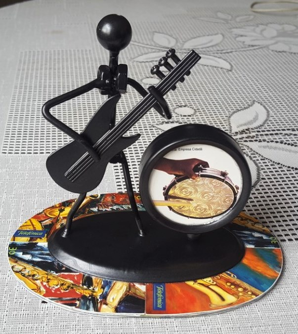 Inclusão da arte feita com cartão telefônico pelo artesão Charles Meira em uma bela peça de ferro.