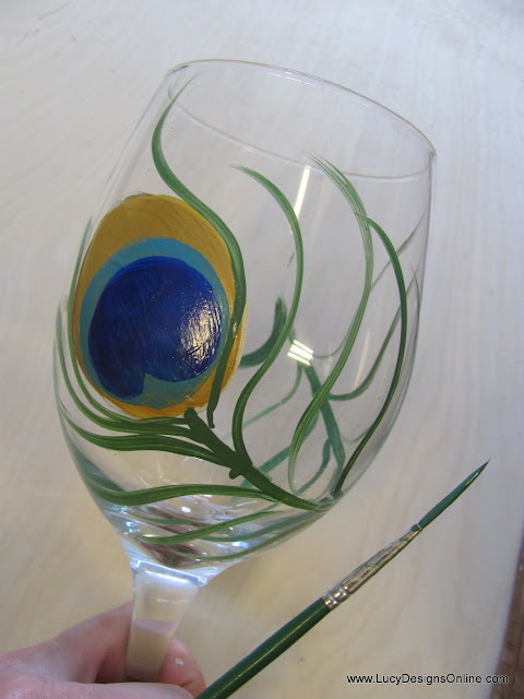 hand painted wine glass with peacock feather and liner brush