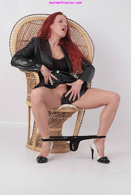 Redhead showing her pleasure in leather