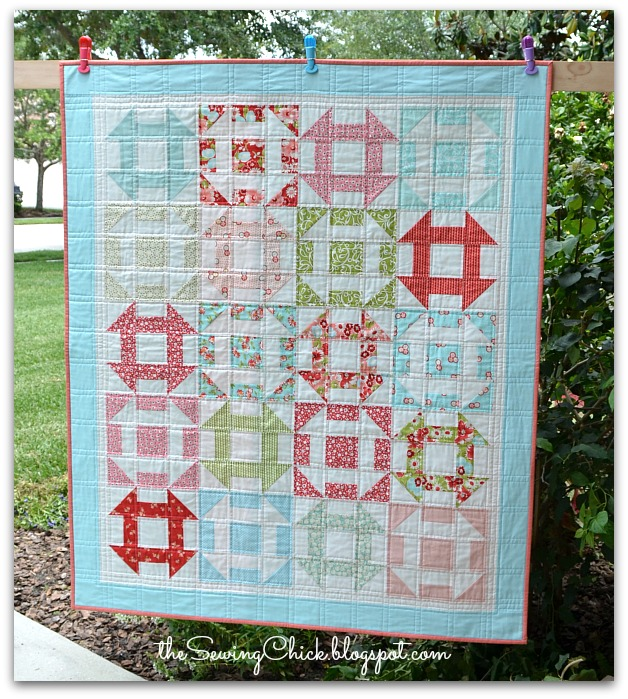a red and aqua modern churn dash quilt
