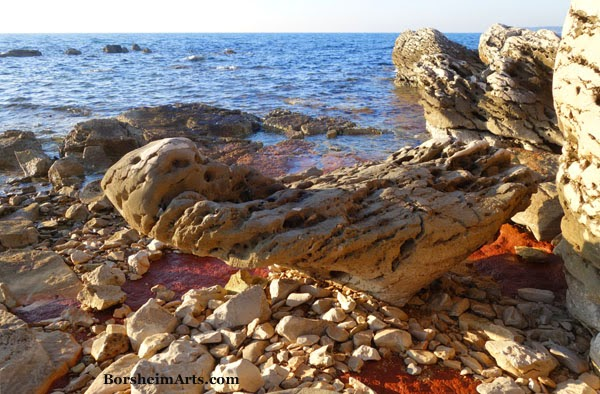 Balancing Triangular stone and red iron-rich clay along the sea north of Umag, Croatia