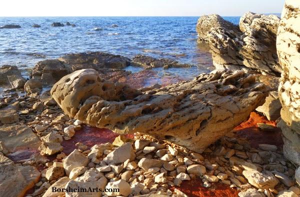 Balancing Triangular stone and red iron-rich clay along the sea north of Umag, Croatia