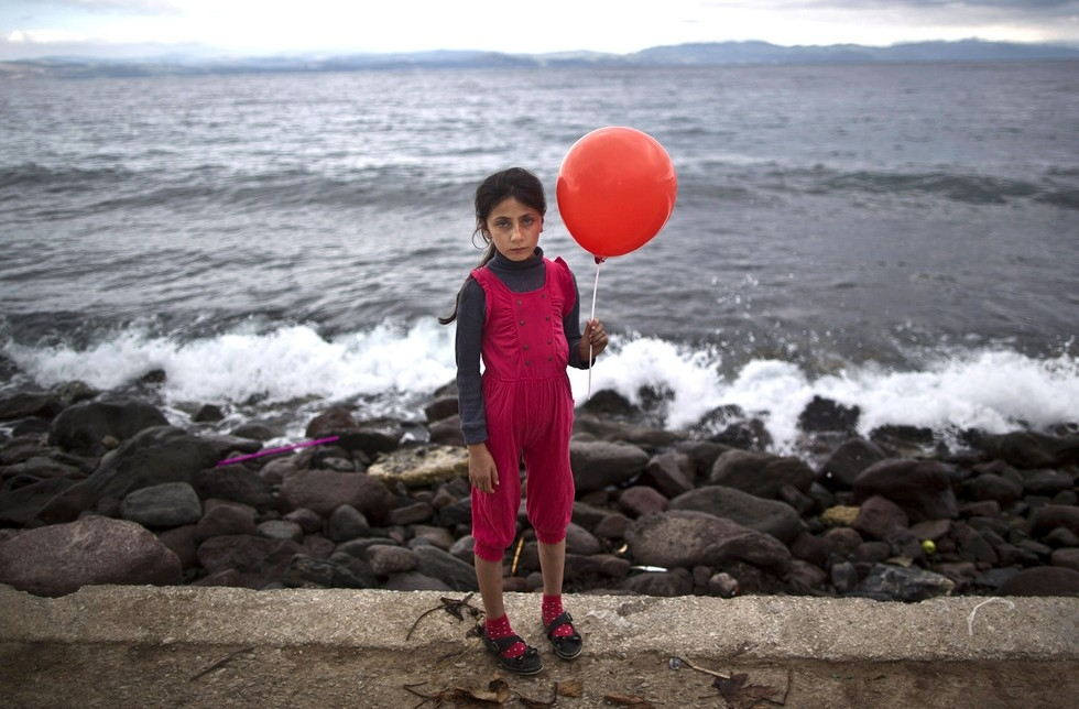 70 Of The Most Touching Photos Taken In 2015 - An exhausted Raghad Faleh, 8, poses for a photo while holding a balloon given to her by volunteers. A few hours earlier, she had arrived in Greece by dingy.