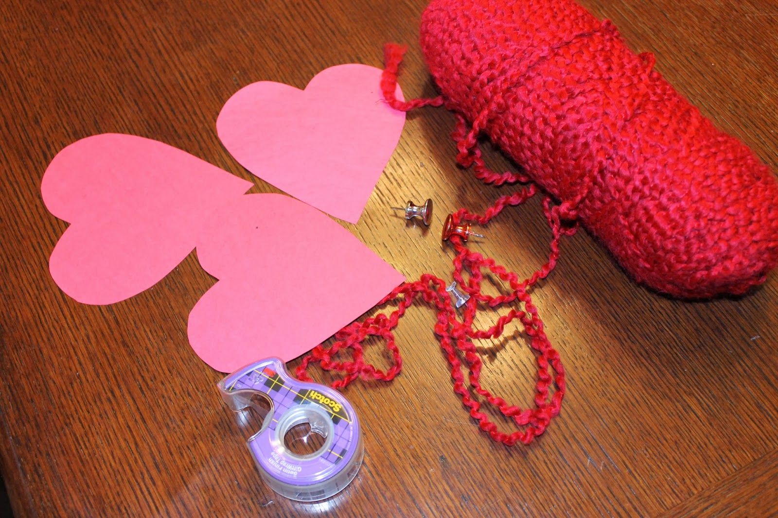 instead of taping all of the hearts to their doors i tied the string to a push pin then i am going to tape the back of the hearts to the string