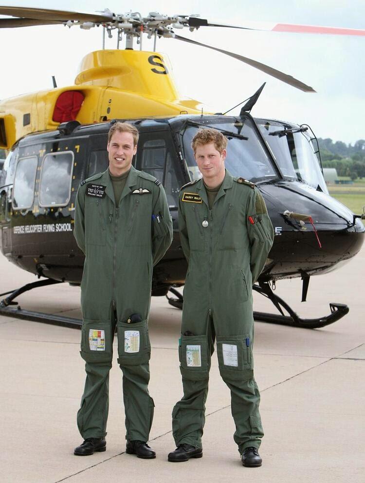 принц Уильям и принц Гарри позируют перед вертолетом «Гриффин» во время фотосессии в аэропорту ВВС Великобритании Шоуберри.