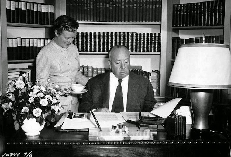 Alfred Hitchcock and wife, Alma at his desk.
