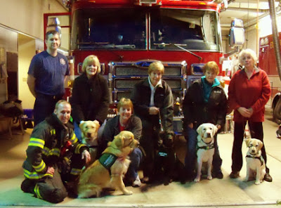 Puppy raisers and their pups posing in front of a fire truck