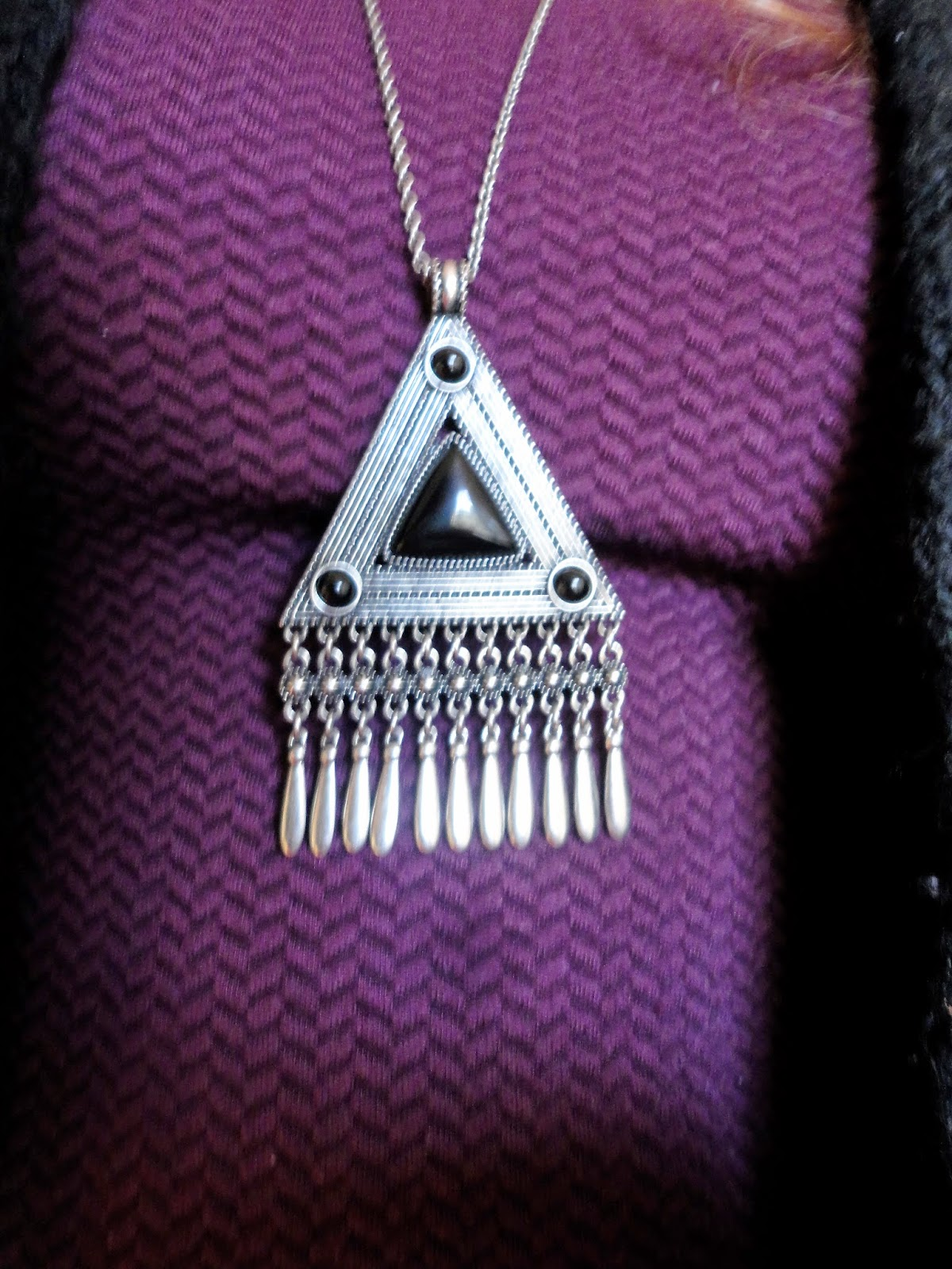 black and silver triangular pendant on purple dress