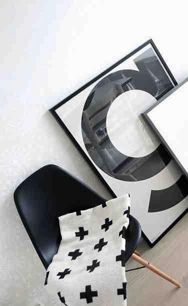 Literaz G w czarnej ramie, koc z krzyżykiem, czarne krzesło Eames