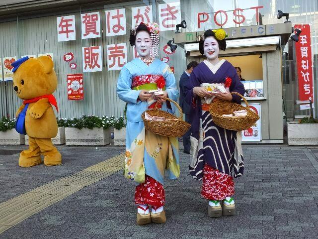 叶子さんと里春さんは年賀はがき「おたのもうします」と街頭で・・・。