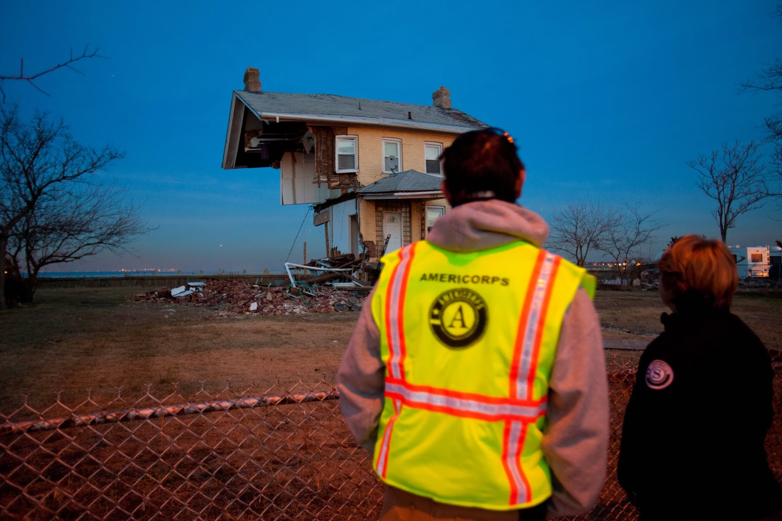 CNCS CEO Wendy Spencer and an AmeriCorps member observe the damage of a 150-year-old home in Union Beach, NJ after Hurricane Sandy