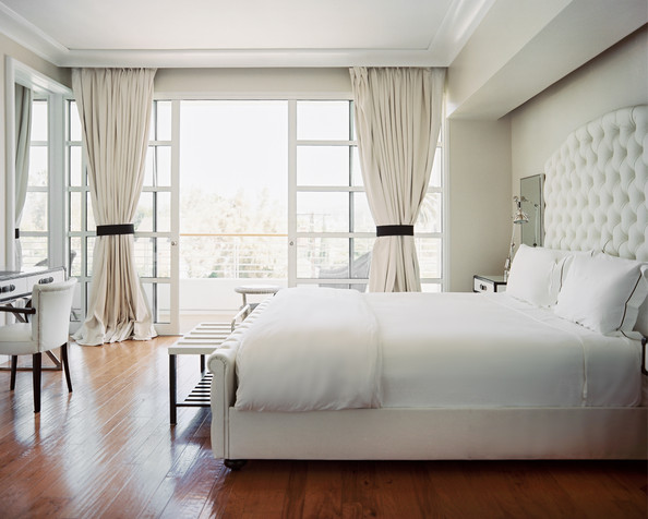 White bedroom with hard wood floor, tufted headboard, french door and a patio