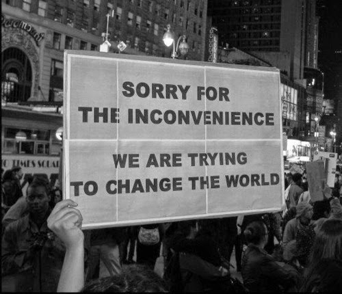 "Photo of a protest sign that reads ""Sorry for the inconvenience. We are trying to change the world."""