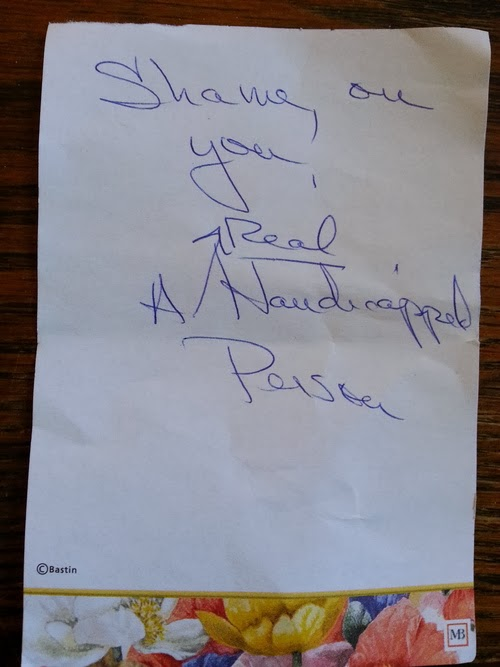 """Handwritten message on personal notepaper reads """"Shame on you! A Real Handicapped Person"""""""