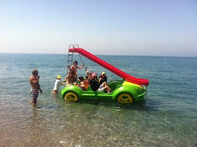 Los afiliados y monitores se montan en un gran hidropedal verde con un tobogán para tirarse al agua