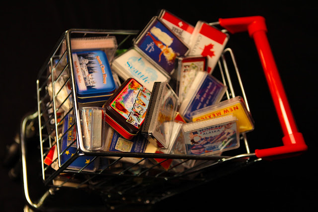 A small shopping cart filled with decks of souvenir playing cards.