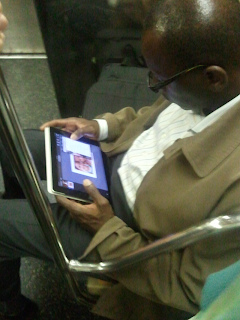 Gentleman using an iPad on the NY subway