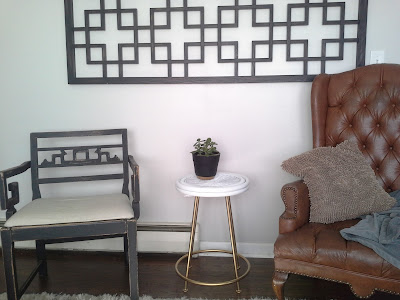 gold brass metal white wicker bamboo rattan side end table, charging station jade plant, greek key black chair, wing back tufted leather chair