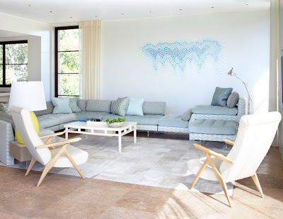 Alternative view of a pastel living room with a sectional sofa, two armchairs with wood legs and arms, large windows and a painted graphic mural of varied shades of blue dots