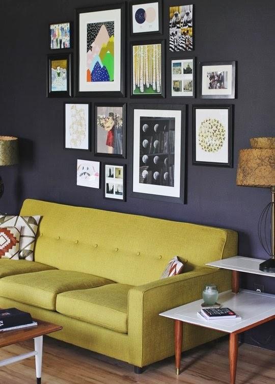parede e molduras escuras realçam as imagens dos quadros