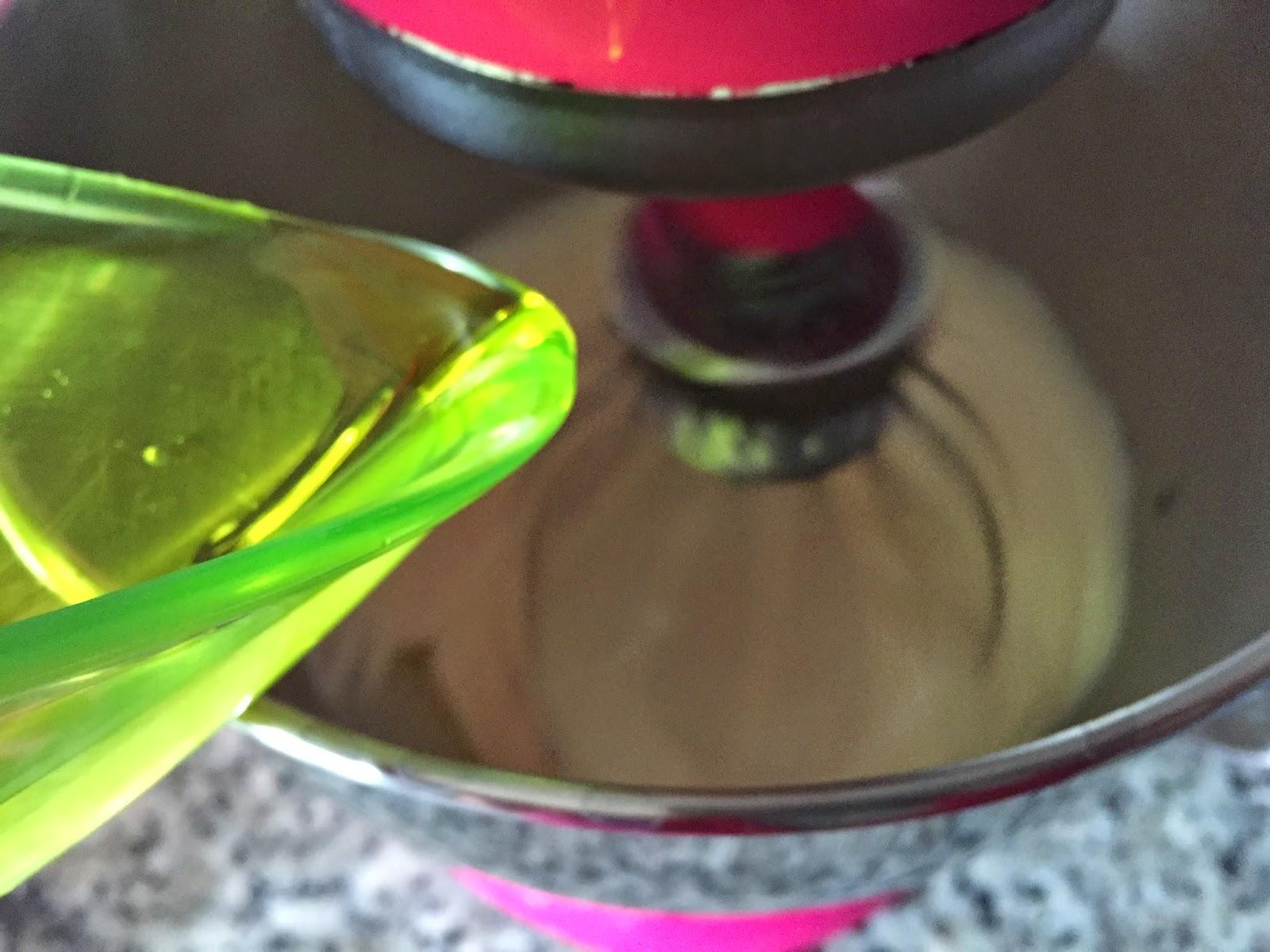 Magdalenas rellenas de mermelada, añadiendo aceite.
