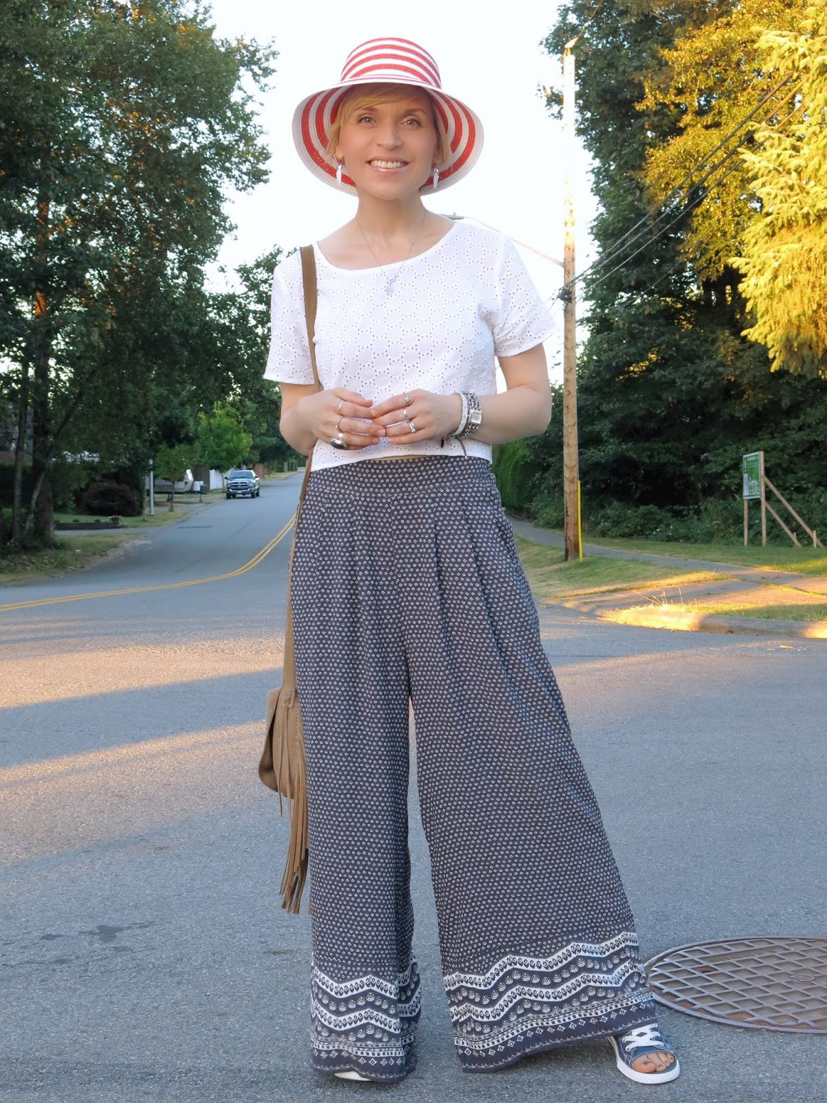 styling palazzo pants with a white eyelet crop top and orange striped hat