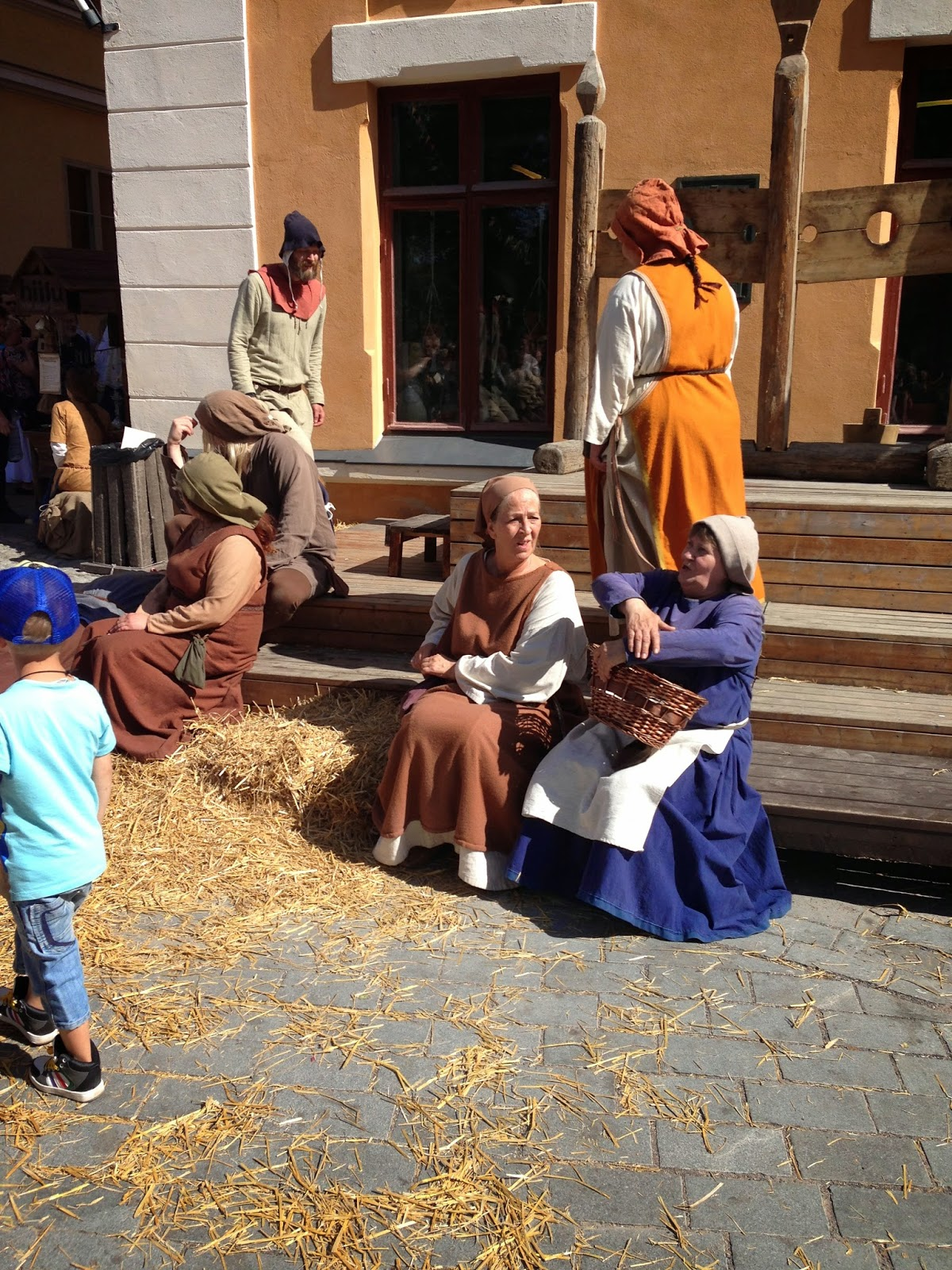 A picture of actors at a medieval market. Medieval people