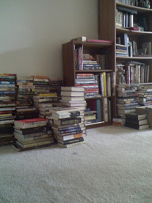 piles of books on the floor, next to full bookshelves