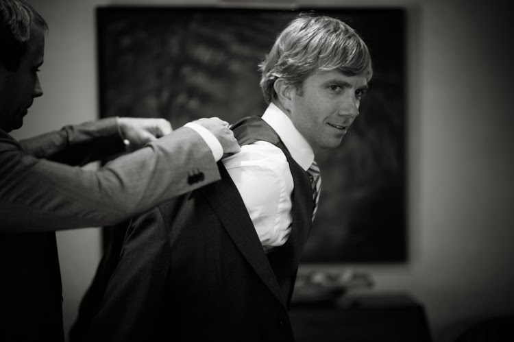 best man helping the groom put on his Armani jacket before the ceremony