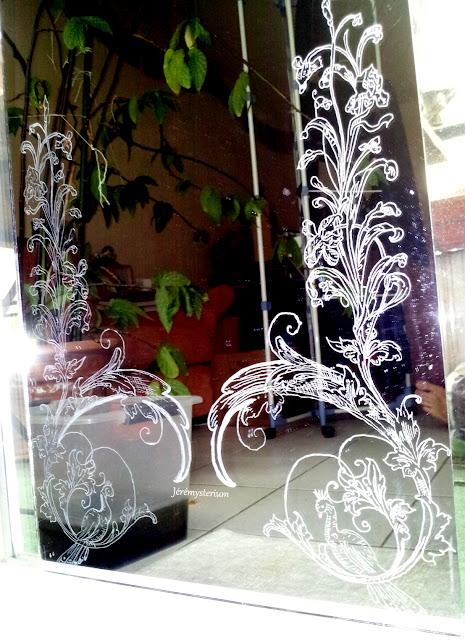 Miroir gravé, style neo art nouveau, représentant deux pans assis sur des branchages arabesques surplombés d'une fleur en branchage