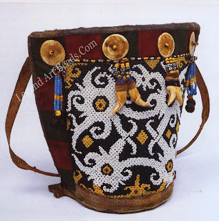 A Dayak beadwork baby carrier (ba), which holds the infant during the first months of life. Shells, beads, and the teeth of bears, crocodiles, and pigs animals with protective spirits are often suspended from the wooden carrier to make a rattling sound, which frightens away evil spirits. An even number of teeth, in this case four, indicates the infant is male. The design of the headed decoration sewn onto a carrier identifies the owner's social class: the baby carrier of a paran (leader and aristocrat) may be covered by an entire human figure in beadwork, while that of a paran iof (someone of slightly lower rank) will only have a partial figure in a stylized or abstract pattern.