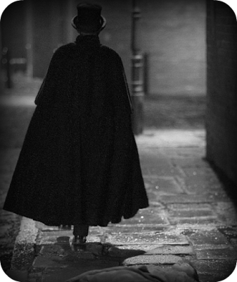 Caped and top-hatted man walks down a Victorian east end London street