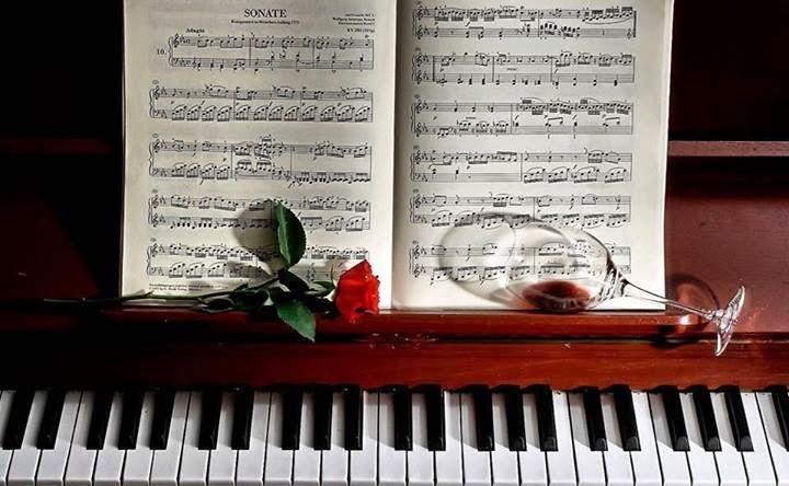 Foto piano partitura rosa roja y copa de vino