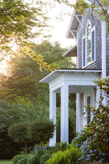 front portico of cedar shingled home at sunset